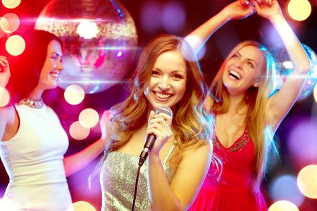 bachelore party: fiesta, a�o nuevo, celebraci�n, amigos, despedida de soltera, cumplea�os concepto - tres mujeres en vestidos de noche bailando y cantando en el karaoke Foto de archivo