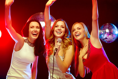karaoke bar: party, new year, celebration, friends, bachelorette party, birthday concept - three women in evening dresses dancing and singing karaoke