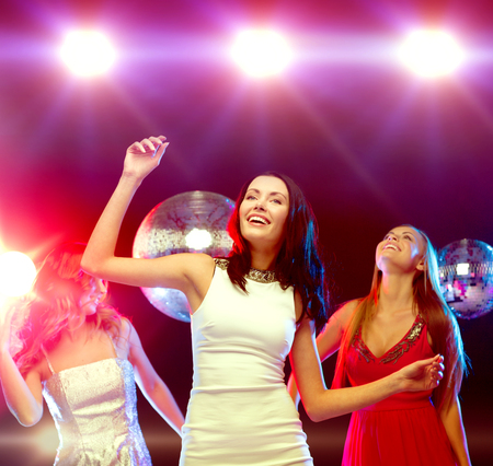 dancing club: party, new year, celebration, friends, bachelorette party, birthday concept - three beautiful woman in evening dresses dancing in the club