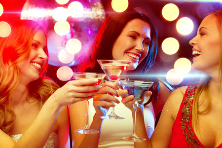 new year, celebration, friends, bachelorette party, birthday concept - three women in evening dresses with cocktails and disco ball Stock Photo