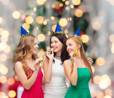 holidays, people and celebration concept - smiling women in party caps blowing to whistles over christmas tree lights background
