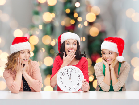 santa helper: winter, holidays, time and people concept - smiling women in santa helper hats with clock over christmas tree background Stock Photo