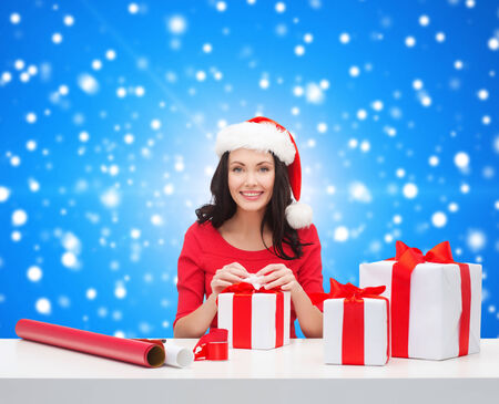 christmas, holidays, celebration, decoration and people concept - smiling woman in santa helper hat with decorating paper packing gift boxes over blue snowing background photo
