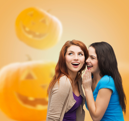 happiness, holidays, firendship and people concept - smiling teenage girls gossiping over halloween pumpkins background photo
