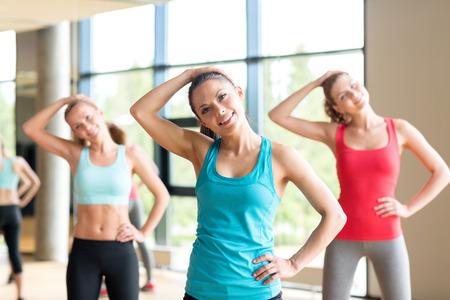 stretching: fitness, deporte, entrenamiento, gimnasio y estilo de vida concepto - grupo de mujeres que trabajan en el gimnasio