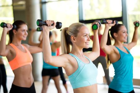 fitnes: fitness, sport, szkolenia i koncepcja życia - grupa kobiet z hantlami w siłowni