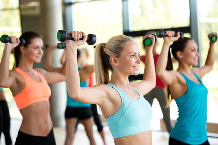 dumbbells: fitness, sport, training and lifestyle concept - group of women with dumbbells in gym