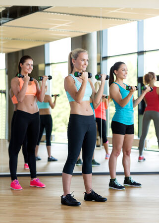 fitness, sport, training, gym and lifestyle concept - group of women with dumbbells in gym photo