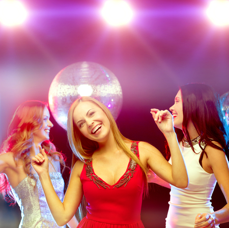 disco girls: new year celebration, friends, bachelorette party, birthday concept - three beautiful woman in evening dresses dancing in the club