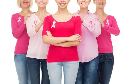 cancer de mama: cuidado de la salud, las personas y el concepto de la medicina - Cerca de la sonriente mujer en camisas en blanco con cintas de color rosa de concienciaci�n del c�ncer de mama m�s de fondo blanco Foto de archivo