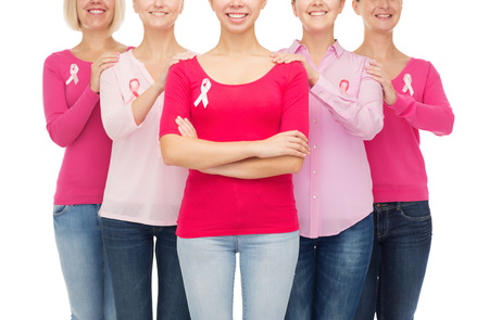 breast girl: healthcare, people and medicine concept - close up of smiling women in blank shirts with pink breast cancer awareness ribbons over white background Stock Photo