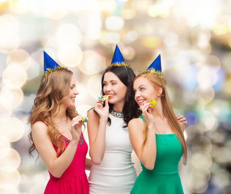 holidays, people and celebration concept - smiling women in party caps blowing to whistles over lights background