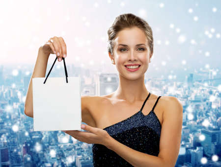 holydays: christmas, sale, advertisement, holydays and people concept - smiling woman with white blank shopping bag over snowy city background
