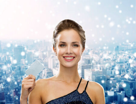 shopping, wealth, christmas, holidays and people concept - smiling woman in evening dress holding credit card over snowy city background photo