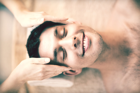 close up of man face in spa salon getting facial massage photo