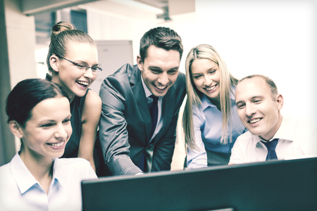 business, technology and office concept - smiling business team with computer monitor having discussion in office photo