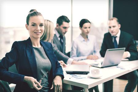 business, technologie en office concept - lachende zakenvrouw met een bril in het kantoor met een team op de rug Stockfoto