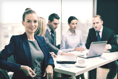 Negocios, la tecnología y la oficina concepto - la sonrisa de negocios con anteojos en la oficina con el equipo en la parte posterior Foto de archivo - 32576993