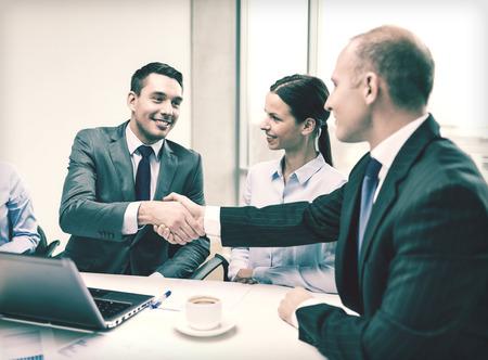 business, technologie en kantoor concept - twee glimlachende zakenman schudden handen in het kantoor Stockfoto