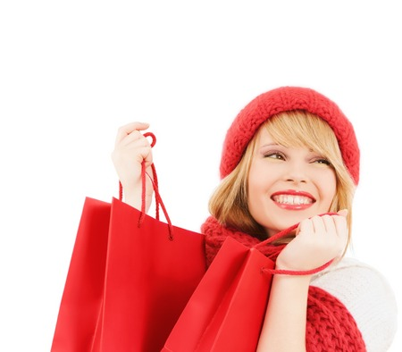 happiness, winter holidays, christmas and people concept - smiling young woman in hat and scarf with red shopping bags over white background photo