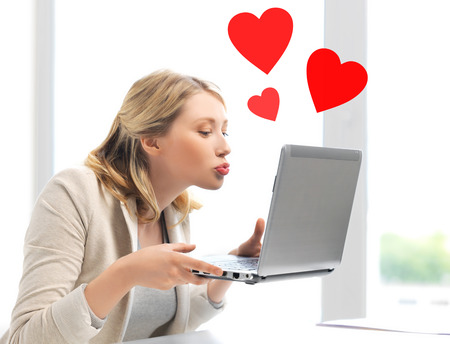 virtual relationships, online dating and social networking concept - woman sending kisses with laptop computer photo