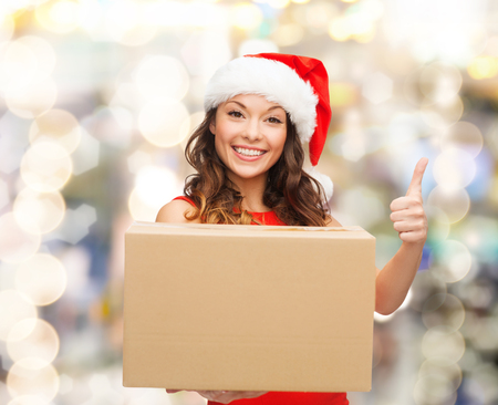 approvement: christmas, winter holidays, delivery, gesture and people concept - smiling woman in santa helper hat with parcel box showing thumbs up over lights background