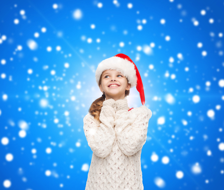 christmas, holidays, childhood and people concept - smiling girl in santa helper hat over blue snowing background photo