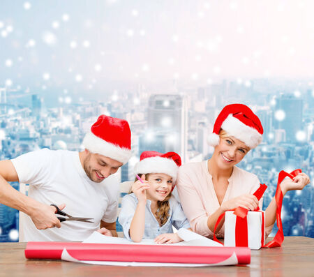 christmas, holidays, family and people concept - happy mother, father and little girl in santa helper hats with gift box and scissors over snowy city background photo