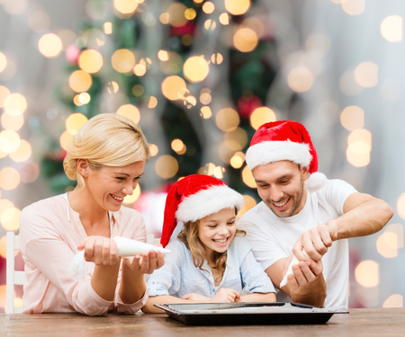 christmas cooking: food, family, happiness and people concept - smiling family in santa helper hats with glaze and pan cooking over christmas tree lights background Stock Photo