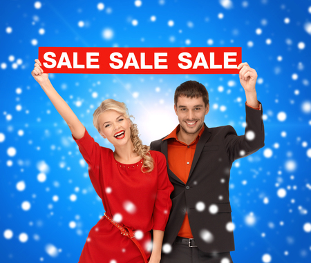 sale, shopping, christmas, holidays and people concept - smiling man and woman in red dress with red sale sign over blue snowing background Stock Photo