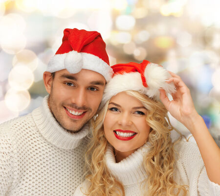 winter, holidays, christmas and people concept - smiling couple in sweaters and santa helper hats over lights background photo