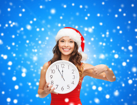 christmas, winter, holidays, time and people concept - smiling woman in santa helper hat and red dress with clock over blue snowing background