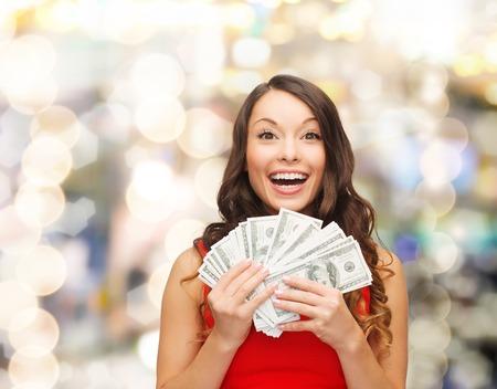 ライトの背景の上ドルのお金を私たちと赤いドレスを着た女性笑顔クリスマス、販売、銀行業、勝利および休日のコンセプト-