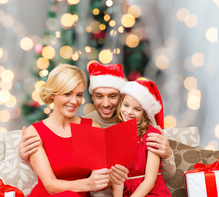 holidays, family and people concept - happy mother, father and little girl in santa helper hats with gift boxes reading geeting card over living room and christmas tree background photo