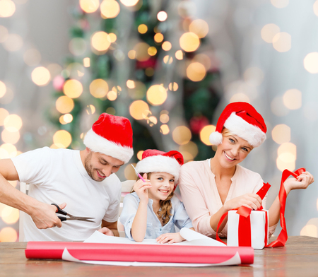 holidays, family and people concept - happy mother, father and little girl in santa helper hats with gift box and scissors over christmas tree lights background photo