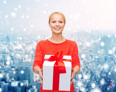 large woman: christmas, holidays, celebration and people concept - smiling woman in red clothes with gift box over over snowy city background