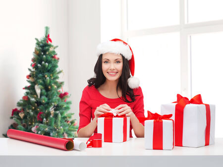holidays, celebration, decoration and people concept - smiling woman in santa helper hat with decorating paper packing gift boxes over living room and christmas tree background photo
