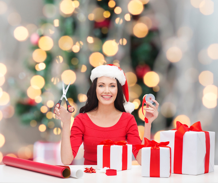 holidays, celebration, decoration and people concept - smiling woman in santa helper hat with scissors packing gift boxes over christmas tree and lights background photo
