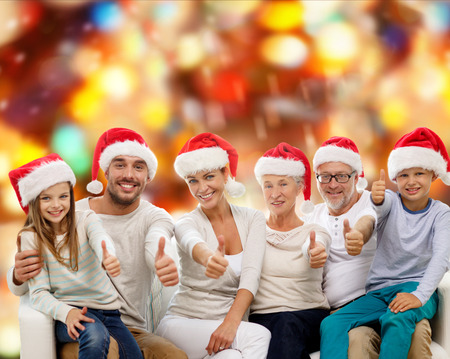 family, generation, gesture, holidays and people concept - happy family in santa helper hats showing thumbs up over red lights background photo