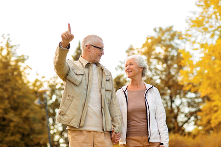 retirement  age: family, age, tourism, travel and people concept - senior couple pointing finger and walking in park Stock Photo