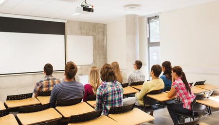 educazione, liceo, lavoro di squadra e la gente il concetto - gruppo di studenti seduti in aula dal retro Archivio Fotografico