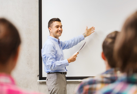 education, high school, technology and people concept - smiling teacher with notepad, laptop computer standing in front of students and showing something on white board in classroom Stock Photo