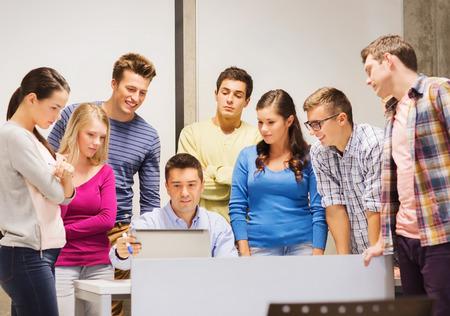 estudiando: la educaci�n, la escuela secundaria, la tecnolog�a y concepto de la gente - grupo de estudiantes sonrientes y profesor de papeles, ordenador port�til en el aula Foto de archivo