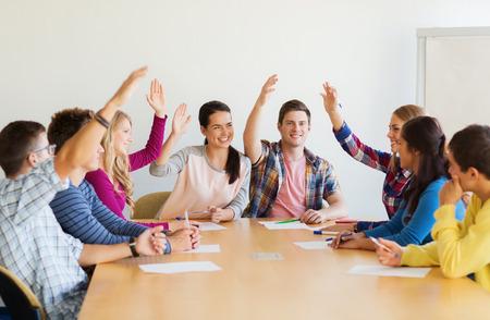 教育、チームワーク、人々 の概念 - 手を上げると室内で投票の論文と笑顔の子供達のグループ