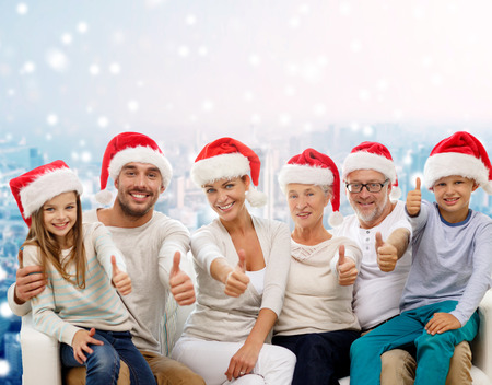family, generation, gesture, holidays and people concept - happy family in santa helper hats showing thumbs up over snowy city background photo