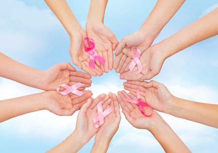 healthcare, people and medicine concept - close up of women hands with cancer awareness ribbons over blue sky background