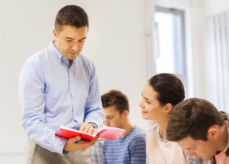 education, high school, teamwork and people concept - group of smiling students and teacher with notebook in classroom