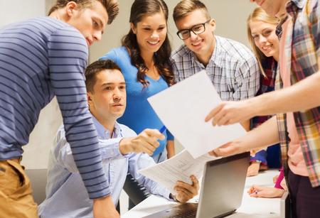 maestra: la educación, la escuela secundaria, la tecnología y el concepto de la gente - grupo de estudiantes sonrientes y profesor de papeles, el ordenador portátil en el aula Foto de archivo
