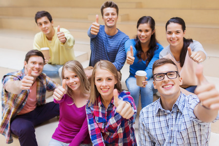 man thumbs up: education, high school, friendship, drinks and people concept - group of smiling students with paper coffee cups showing thumbs up gesture Stock Photo