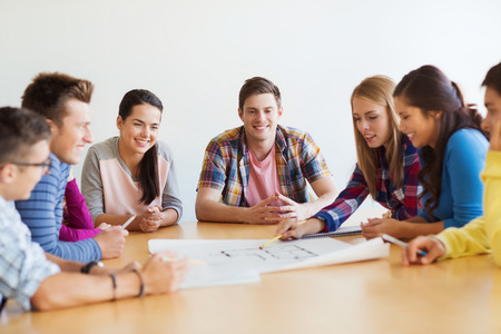 building plans: education, school, architecture and people concept - group of smiling students with blueprint meeting indoors Stock Photo